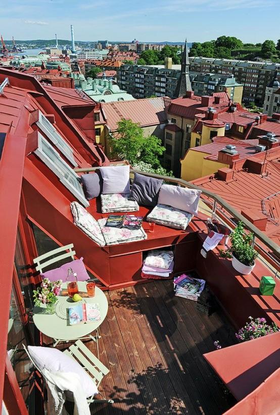 una colorata terrazza estiva con piante in vaso e fiori, tessuti estivi stampati, semplici mobili pieghevoli in metallo