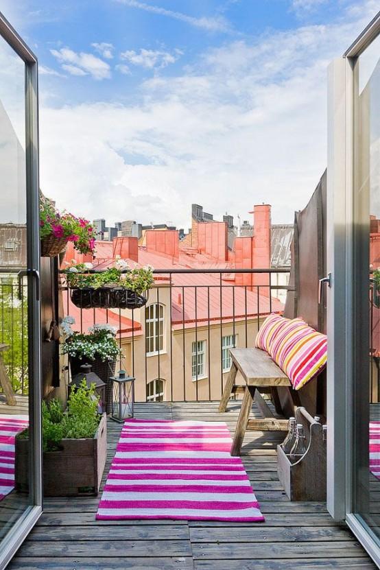 un piccolo ma luminoso balcone estivo con una semplice panca in legno, tessuti a strisce colorate, vegetazione in vaso e fiori per prendere il sole