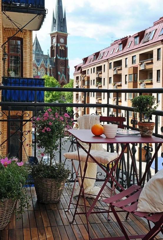 un balcone estivo chic e divertente con mobili in metallo rosa, vegetazione in vaso e fiori è uno spazio semplice e chic per godersi l'aria fresca