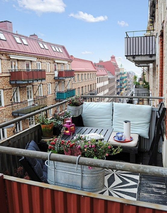 un piccolo balcone estivo con mobili in legno, tessuti neutri, una lanterna rosa a candela e piante e fiori in vaso
