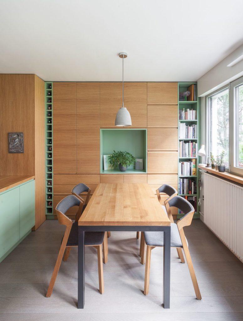 La zona pranzo è realizzata con un set contemporaneo, con un contenitore integrato e mensole