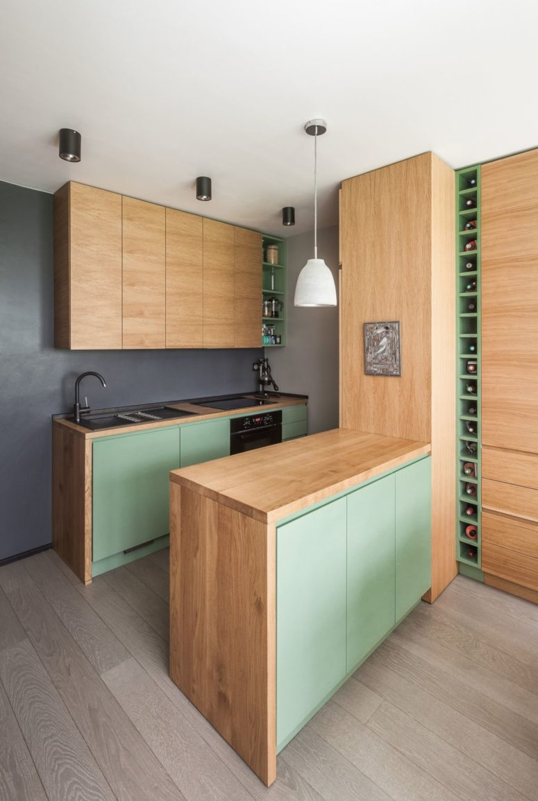La cucina è caratterizzata da armadi di colore chiaro e porte verde menta: tutto il necessario è qui