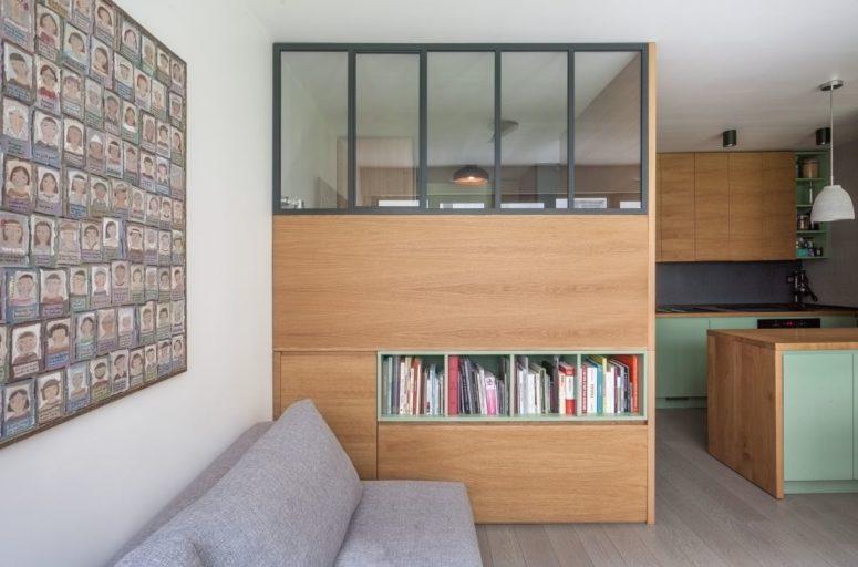 Il soggiorno è composto da un divano grigio, un grande contenitore che funge anche da divisorio