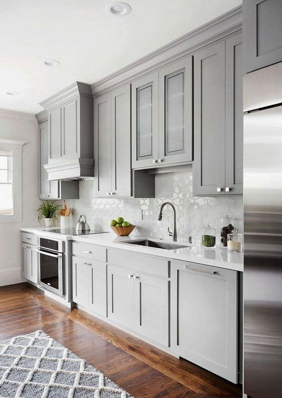 un'elegante cucina grigio tortora contemporanea con alzatina in piastrelle bianche e controsoffitti più un ricco pavimento macchiato