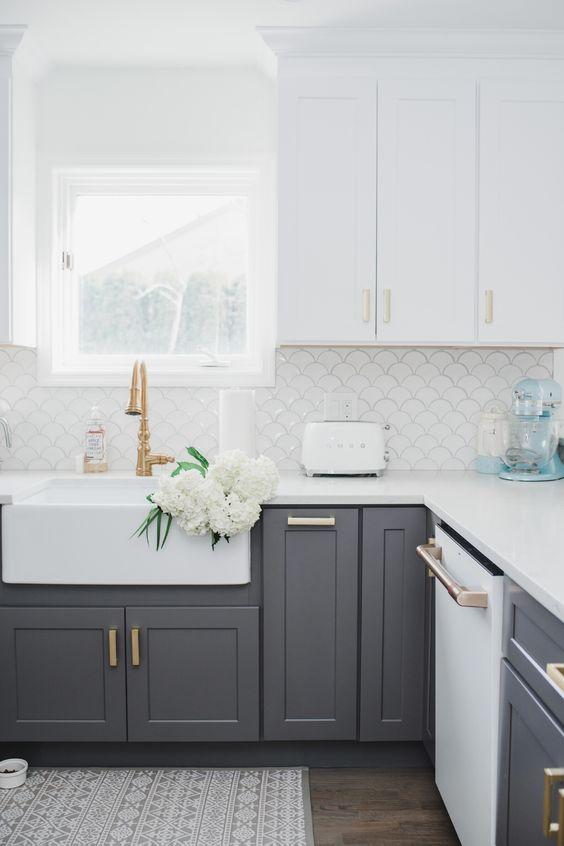 una cucina contemporanea con mobili superiori bianchi e inferiori grigi, maniglie in oro e ottone più un alzatina in scala di pesce bianco