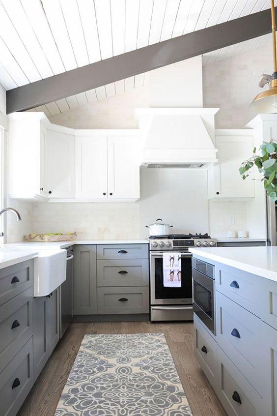 un'elegante cucina bicolore con mobili superiori bianchi e inferiori grigio chiaro, maniglie nere e travi in legno scuro
