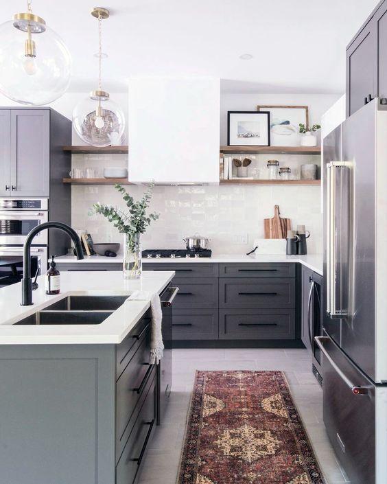 una cucina contemporanea con mobili grigi, cappa bianca e alzatina piastrellata e ripiani bianchi più un tappeto boho