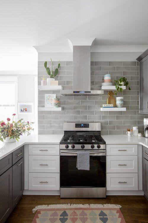 un'elegante cucina bicolore con armadi grigi e bianchi, alzatina in piastrelle grigie e ripiani bianchi