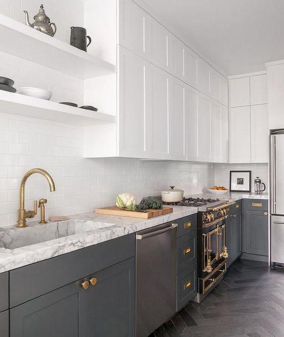 una cucina contemporanea con mobili inferiori grigi, bianchi superiori, tocchi in oro e ottone, ripiani bianchi