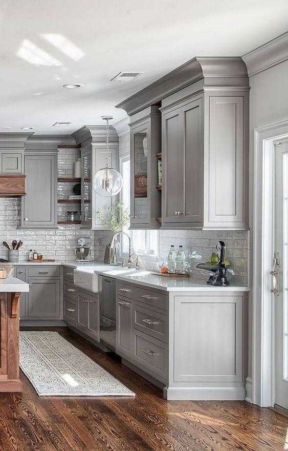 una cucina rustica in grigio tortora con alzatina in piastrelle bianche, una lampada a bolle e un ricco legno tinto per un tocco caldo
