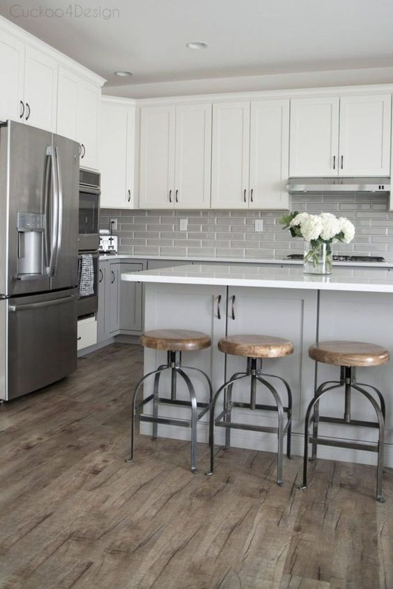 una cucina moderna della metà del secolo con mobili inferiori grigio tortora, mobili superiori bianchi, alzatina piastrellata grigia e isola cucina grigia