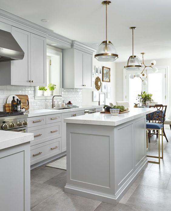 una cucina moderna della metà del secolo con armadi tortora, tocchi d'oro e lampade e lampadari chic per un'atmosfera elegante