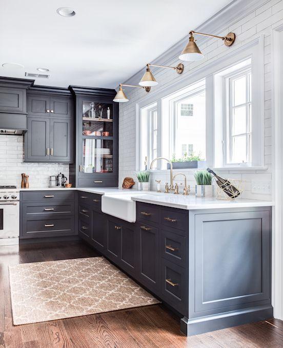 una cucina moderna della metà del secolo con armadi grigio grafite, ripiani bianchi, lampade e maniglie in ottone più piastrelle bianche sul backsplash