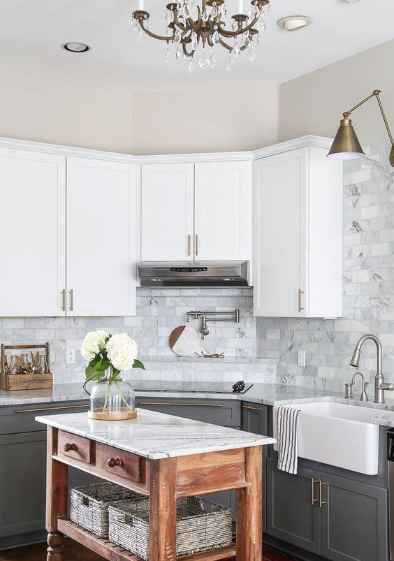 una cucina da fattoria con mobili bianchi superiori, quelli grigio grafite, un alzatina in piastrelle di marmo e un'isola da cucina macchiata