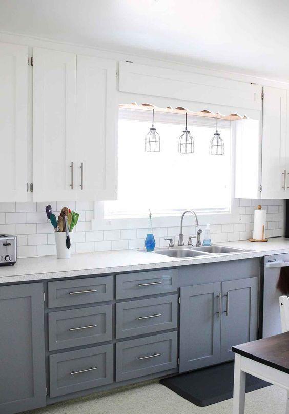 una moderna cucina da fattoria con mobili bianchi superiori, grigi inferiori, lampade a sospensione e tocchi metallici qua e là