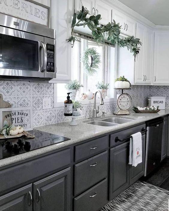 una cucina elegante con mobili superiori bianchi, inferiori grigio grafite, alzatina in mosaico e ripiani in pietra