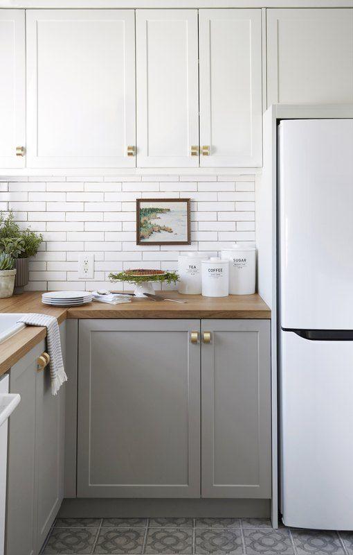una cucina bicolore con pensili bianchi superiori, inferiori tortora, ripiani in legno e maniglie oro