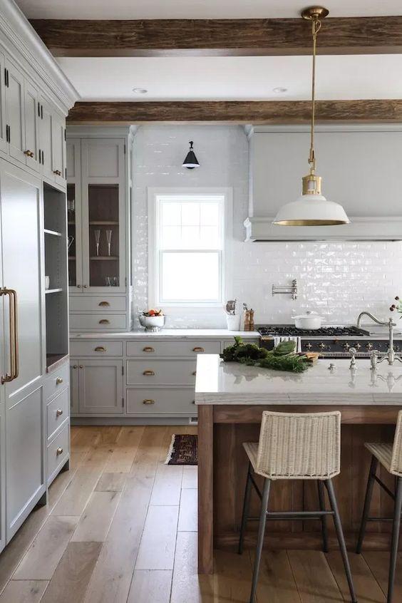 una cucina vintage con mobili tortora, alzatina in piastrelle bianche, lampade bianche e travi in legno più un'isola della cucina