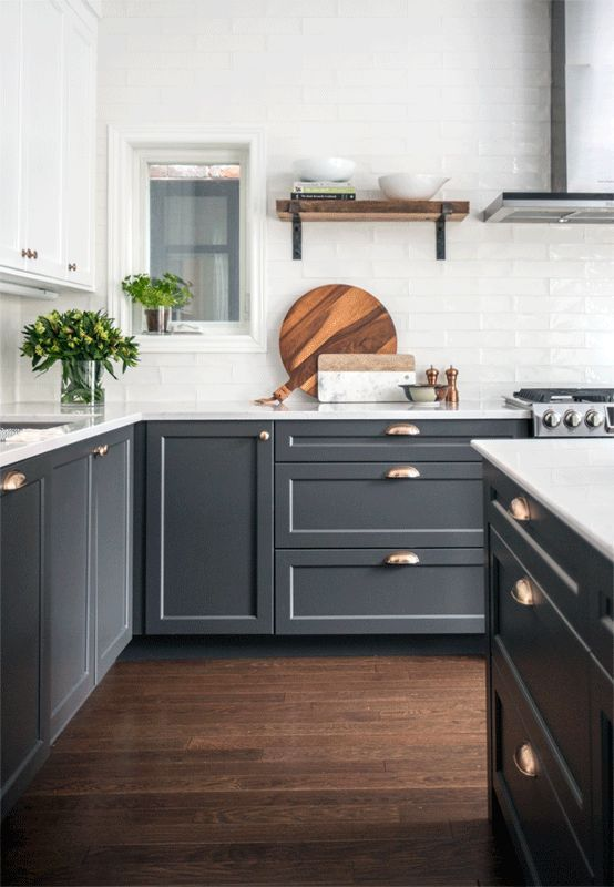 uno spazio elegante e contemporaneo con mobili superiori bianchi e inferiori grigio grafite, dettagli in ottone e oro