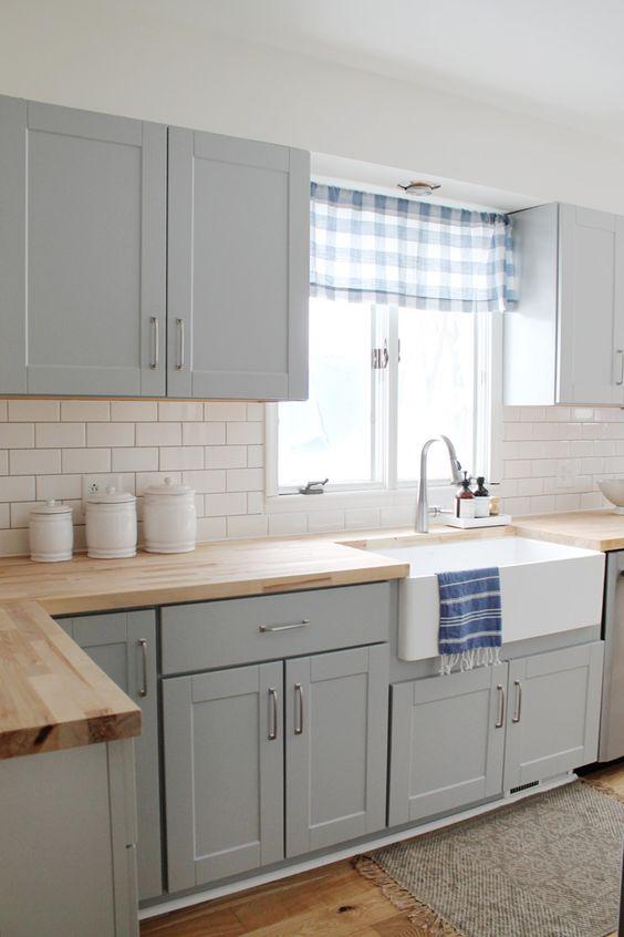 una cucina ariosa con armadi tortora, un backsplash in piastrelle bianche della metropolitana e piani di lavoro in legno sembra fresca e audace