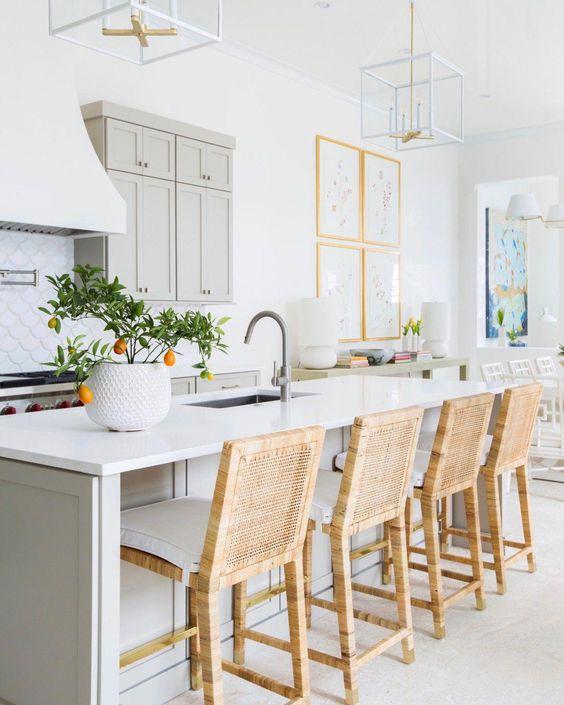 una cucina ariosa con armadi tortora e un'isola della cucina, ripiani in pietra bianca, sgabelli in vimini e lampadari a telaio