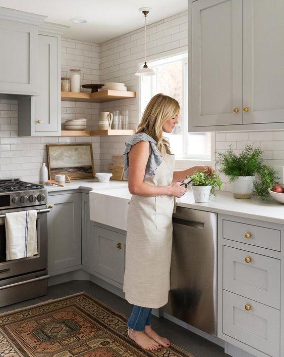 armadi tortora, alzatina in piastrelle bianche e controsoffitti bianchi, mensole in legno e un tappeto boho per un look chic