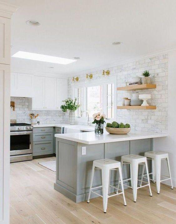 una cucina eterea con mobili inferiori tortora, bianchi superiori, controsoffitti bianchi e pareti piastrellate più tocchi d'oro