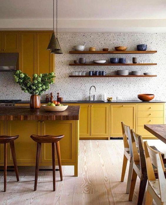 una cucina audace con armadi color senape, ripiani in legno, un backsplash in piastrelle bianche e tocchi di legno qua e là