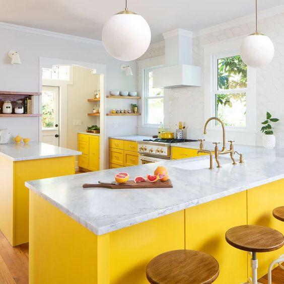 una cucina luminosa fatta con armadi gialli, ripiani in pietra bianca e tutto tutto bianco per un look chic e audace