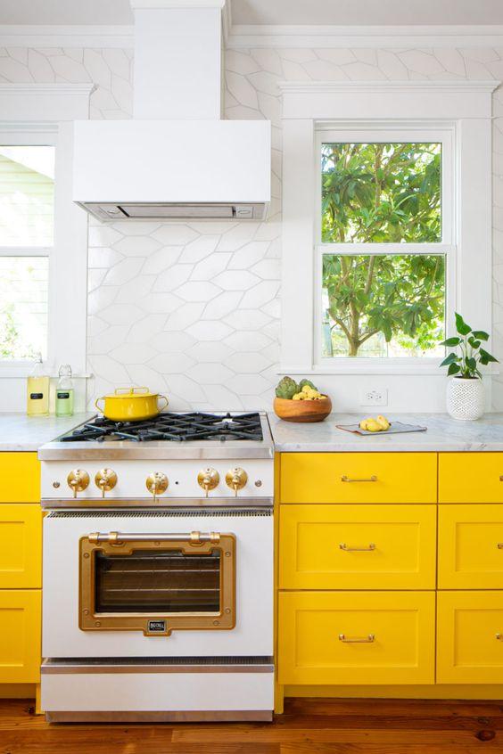 una cucina luminosa con armadi giallo sole, un accattivante alzatina in piastrelle bianche e tutto tutto bianco per una sensazione di freschezza