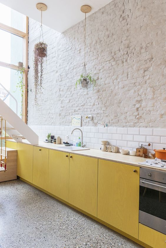una cucina contemporanea audace con armadi in compensato giallo, controsoffitti neutri, un backsplash in piastrelle bianche della metropolitana e un muro di mattoni