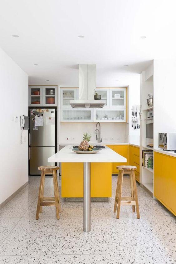 una cucina contemporanea fatta con mobili gialli e bianchi soleggiati, con ripiani bianchi e un pavimento a mosaico sembra fresca