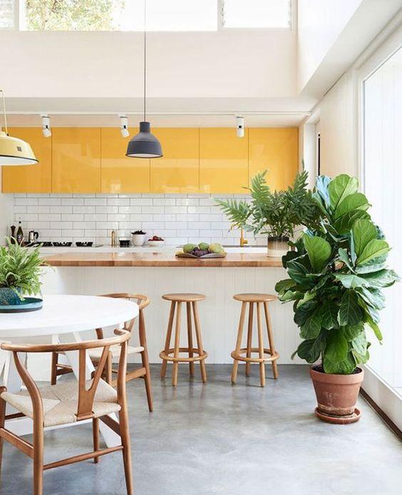 una luminosa cucina tropicale fatta con mobili superiori gialli e tutto tutto bianco più un lucernario per rinfrescarsi