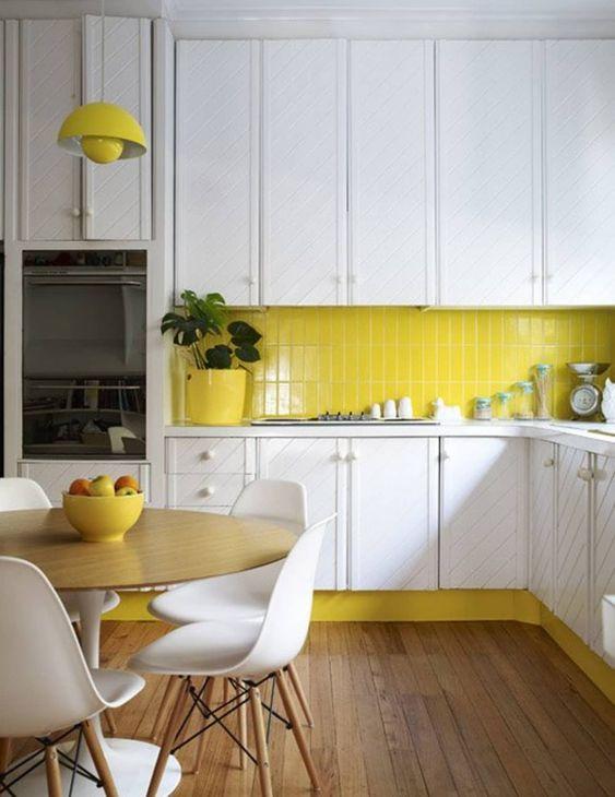 una cucina contemporanea fatta in giallo limone e bianco, con armadi materici e un pavimento in legno sembra audace