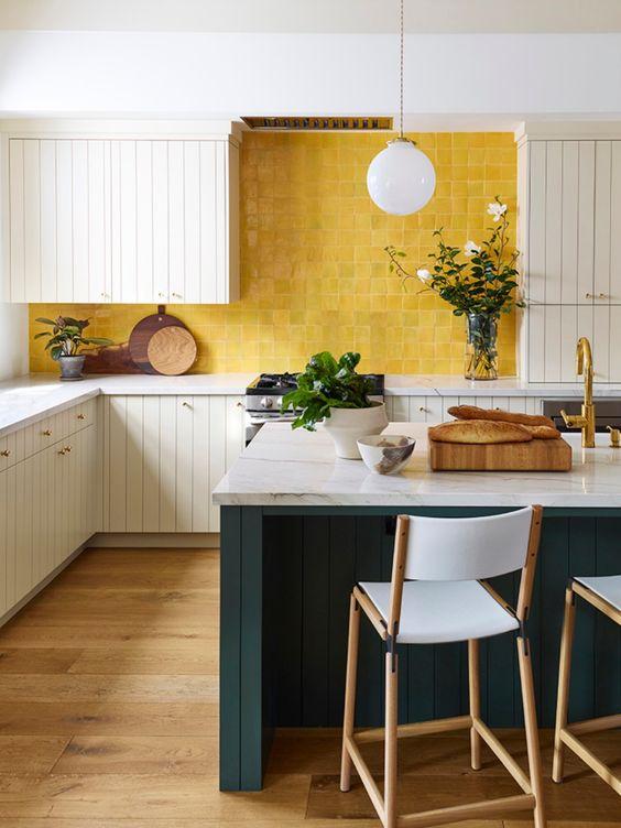 una cucina luminosa con armadietti bianchi, alzatina piastrellata gialla e isola cucina verde acqua con ripiani in pietra