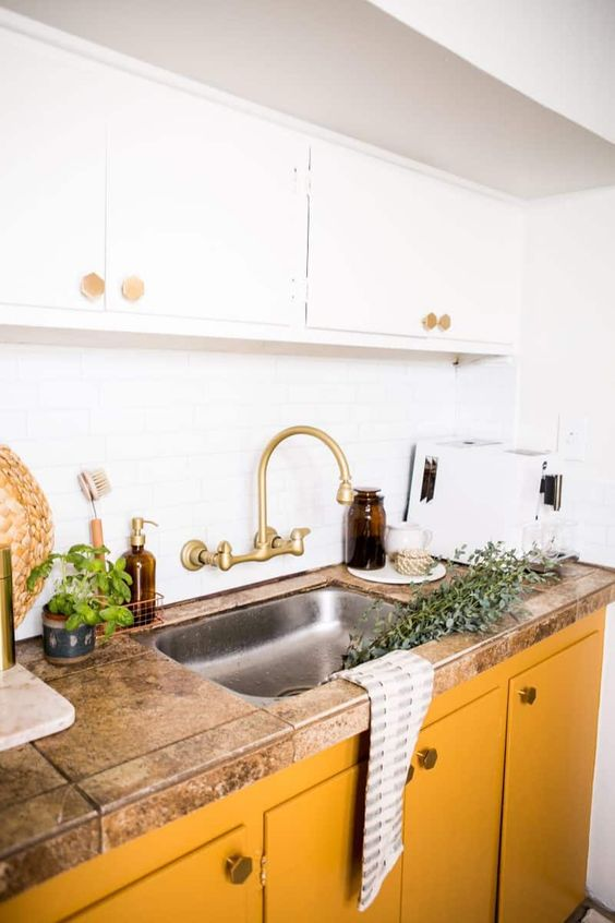 una cucina chic con mobili superiori bianchi e quelli inferiori crema al burro più un piano di lavoro in pietra e tocchi in ottone sembra fresca