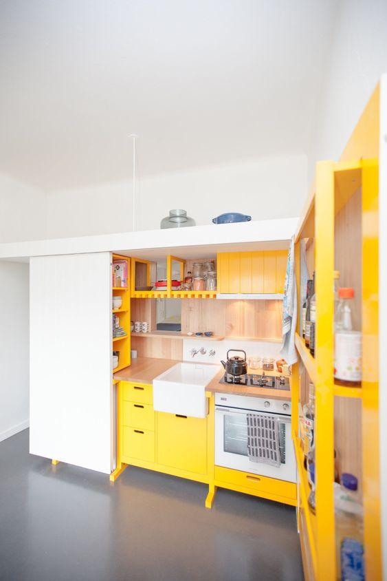 una mini cucina contemporanea realizzata in giallo sole e con tocchi di legno naturale più built-in è audace
