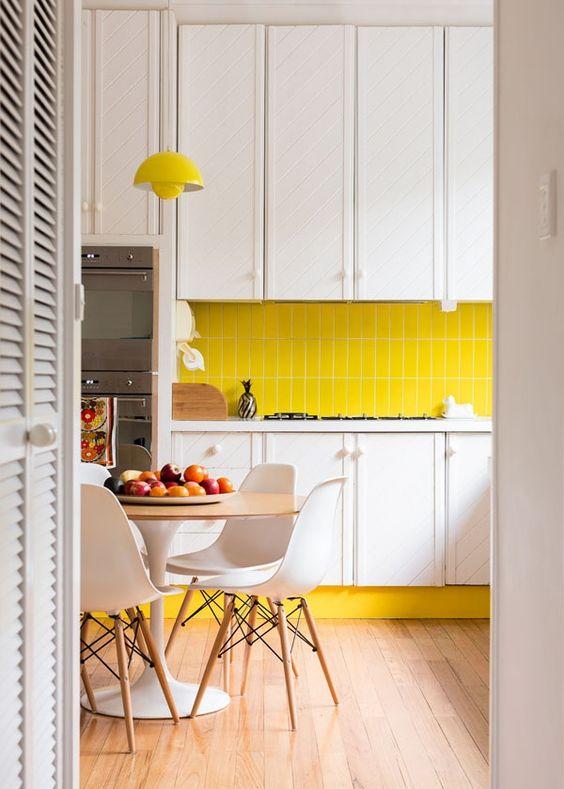 una cucina contemporanea con armadi bianchi, un backsplash di piastrelle giallo brillante e una lampada, sedie bianche e neutri
