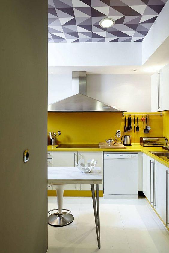 una cucina bianca contemporanea resa audace con un backsplash giallo e controsoffitti più elettrodomestici stele senza macchie