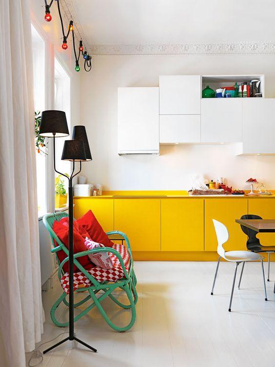 una cucina contemporanea con armadi bianchi e gialli e luci integrate, oltre a tocchi colorati per di più