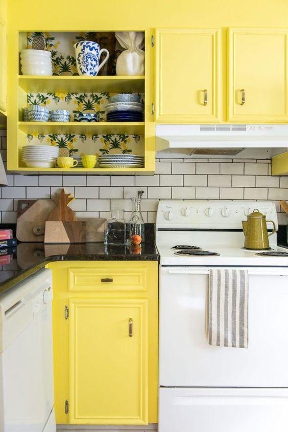 una cucina retrò in bianco e giallo, con elettrodomestici bianchi e un backsplash in piastrelle bianche della metropolitana più controsoffitti neri