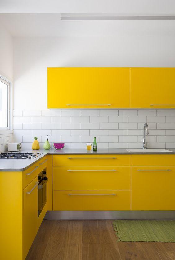 una cucina contemporanea super luminosa con armadi gialli, un backsplash in piastrelle bianche della metropolitana e un pavimento in legno sembra wow