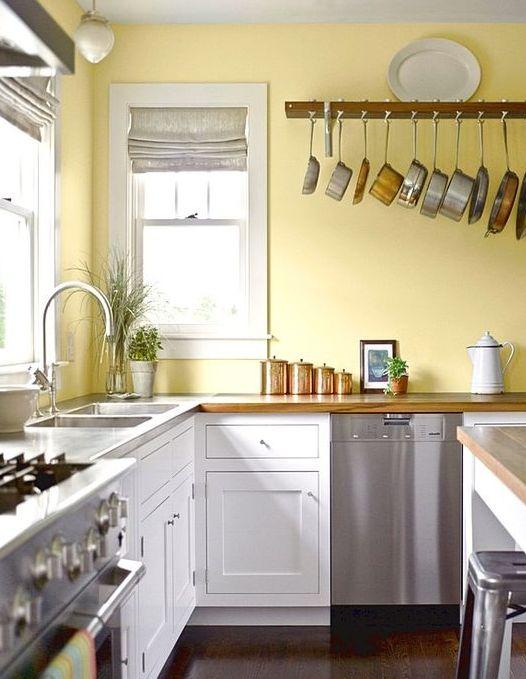una cucina retrò con un muro giallo limone, armadi bianchi, elettrodomestici in metallo e tocchi di rame