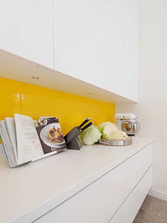 una cucina bianca minimalista con un backsplash di vetro giallo brillante è super cool ed extra audace