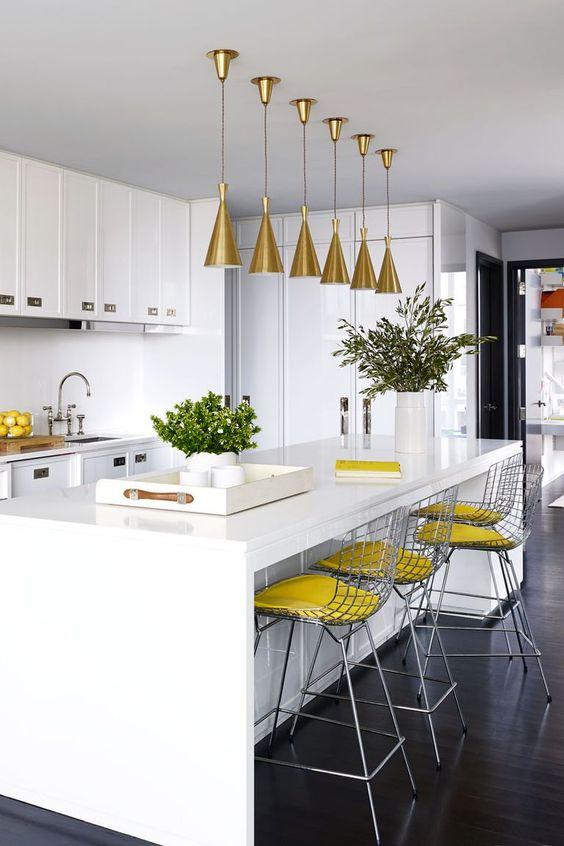 una cucina bianca con lievi accenti gialli: sgabelli gialli e limoni in una ciotola più lampade dorate sull'isola