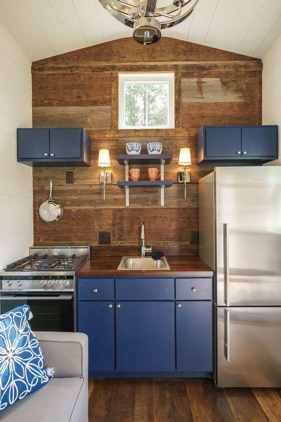 una piccola cucina con un muro in legno, armadietti blu mirtillo per un tocco di colore