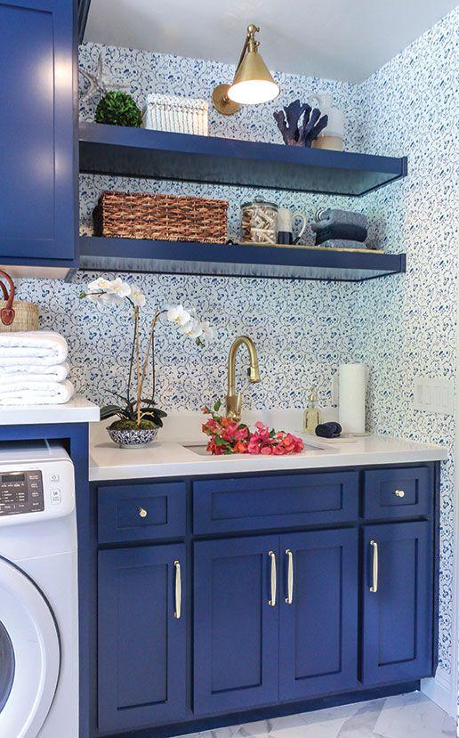 una piccola cucina fatta con armadietti blu mirtillo, mensole e bianco per massimizzare