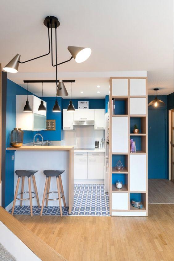 una minuscola cucina in bianco e blu mirtillo, con tocchi di grigio grafite e alcune stampe