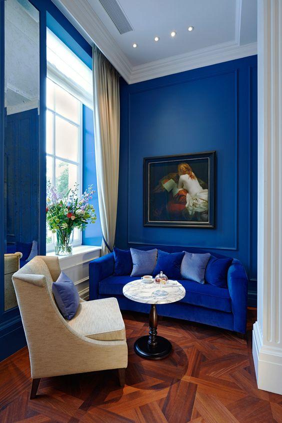 un soggiorno raffinato ma minuscolo con pareti blu mirtillo e un divano blu brillante per un tocco audace