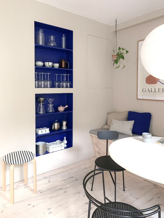 un angolo da pranzo neutro con una nicchia blu mirtillo per riporre e cuscini abbinati che aggiungono colore allo spazio